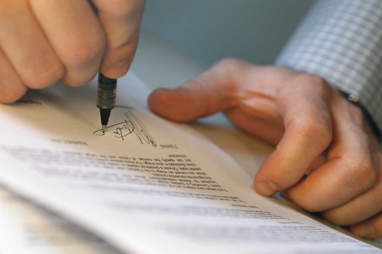 Hands signing document Opening a Small Business Bank Account with Bad Personal Credit